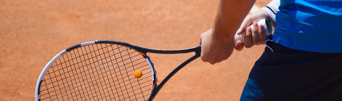 A man is holding a tennis braket